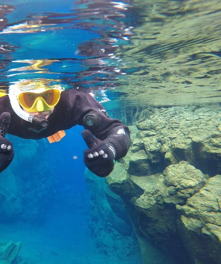 Довольный турист с маской для снорклинга, в разломе Сильфра в Исландии.