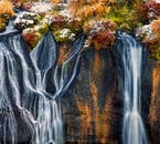 In the autumn, the gentle rivulets at Hraunfossar fall over cliffs characterised by the warm reds and oranges of the surrounding autumnal flora.