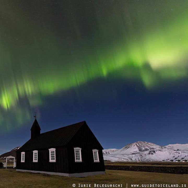 Northern Lights dancing over the jet-black church at Búðir in Snæfellsnes.