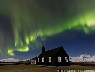 Northern Lights dancing over the jet-black church at Búðir in Snæfellsnes.