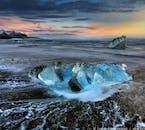 Góra lodowa lśniąca na czarnej, piaszczystej plaży położonej w pobliżu pięknej laguny Jökulsárlón.