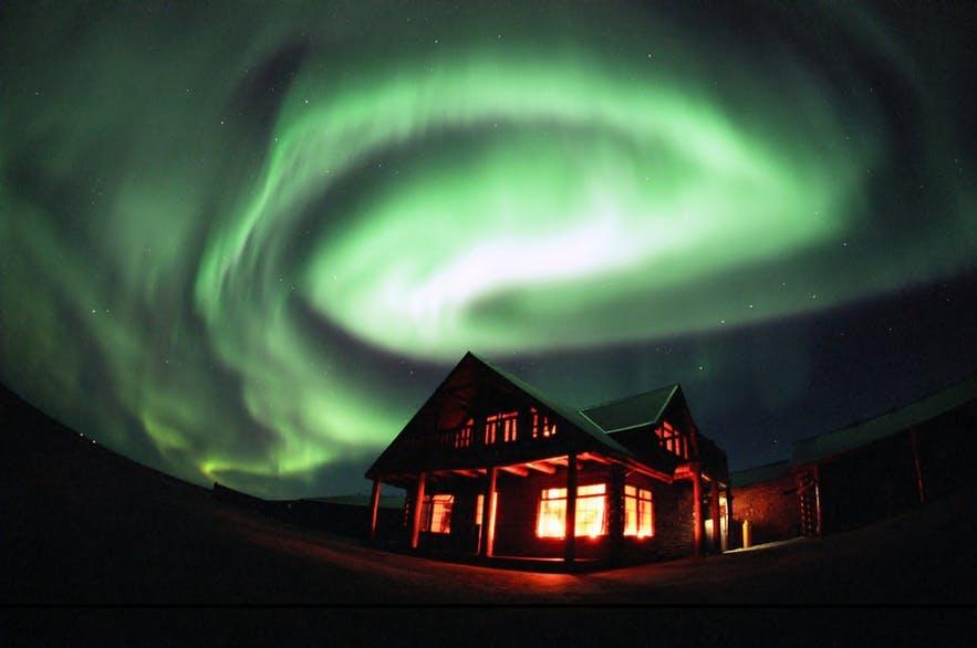 Nordlichter über einer abgelegenen Unterkunft in der Natur Islands.