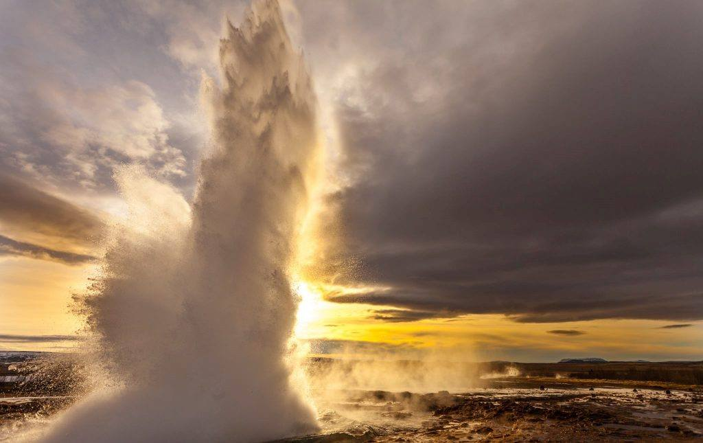 The hot spring Strokkur erupts in Geysir geothermal area in front of a moody sky,
