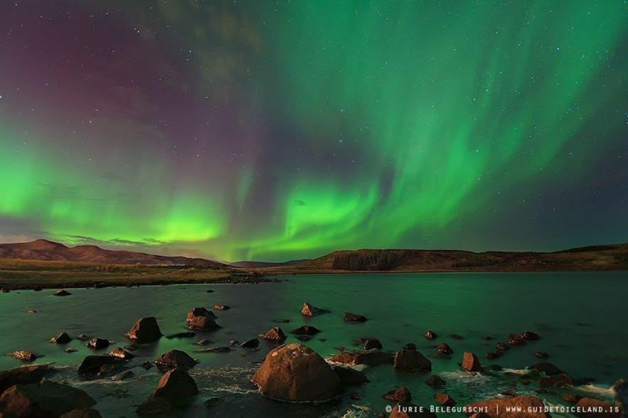 Das Grün der Polarlichter schimmert im See darunter