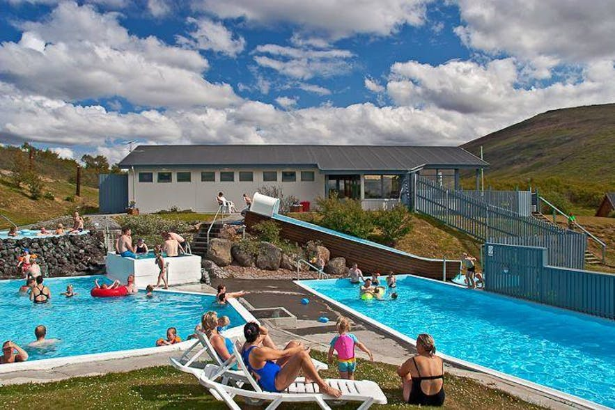 People lounging by the pool in Husafell