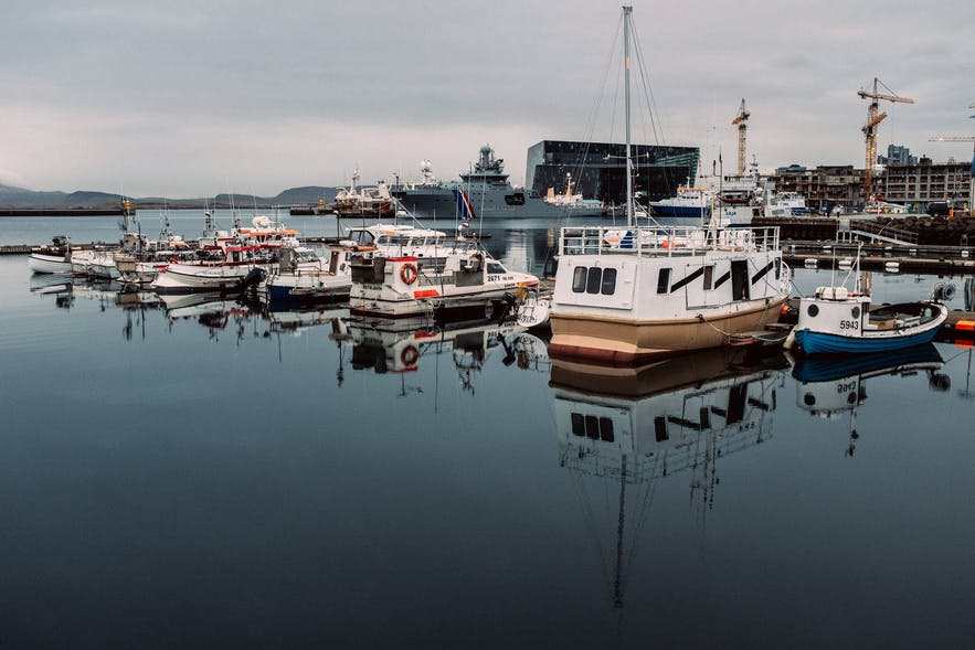 Small boats in Reykjavik harbour with Harpa Concert Hall in the background