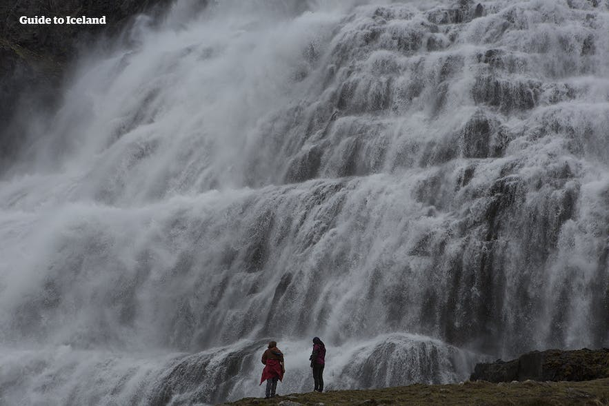 Two figures stand by Dynjandi waterfall