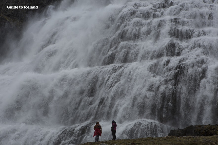 Two figures stand by Dynjandi waterfall in Iceland.