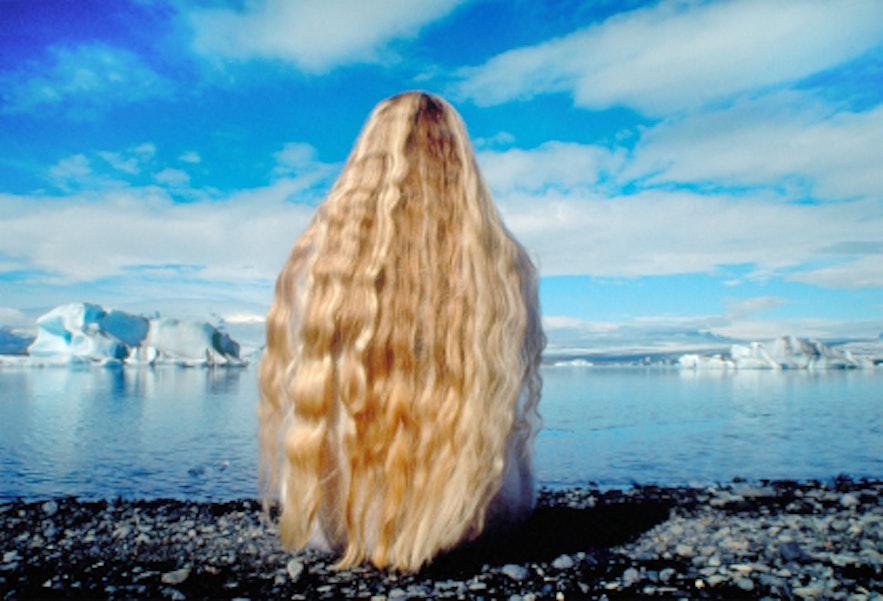 ヨークルスアゥルロゥン氷河湖を眺めるアイスランドの女性