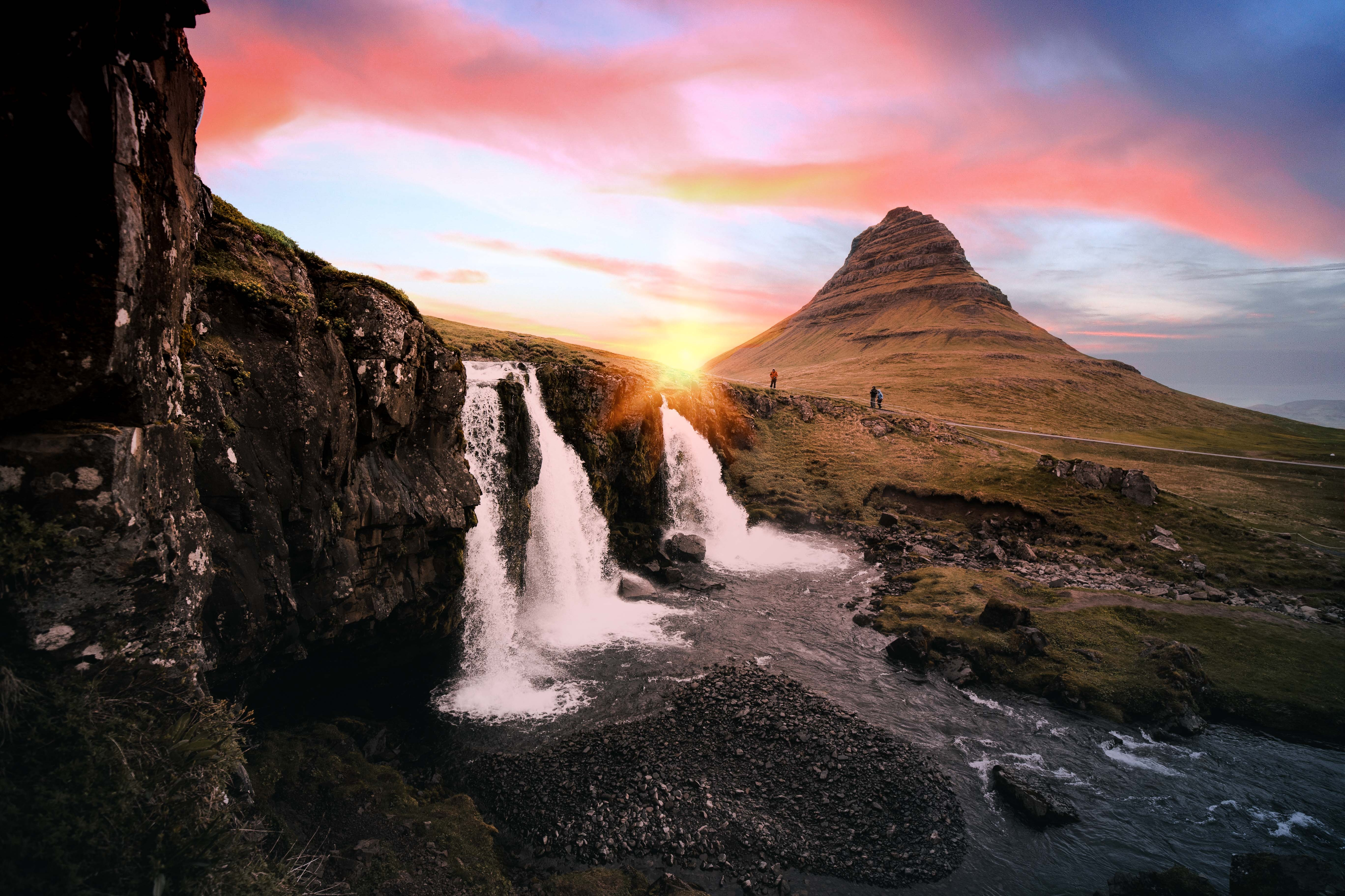 Kirkjufellsfoss-vandfaldet løber i forgrunden, mens solen går ned