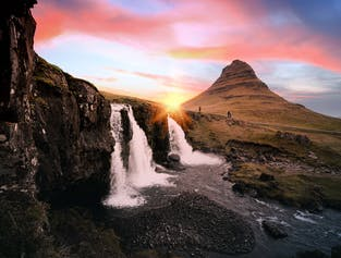Kirkjufellsfoss waterfall trickles in the foreground as the sun sets