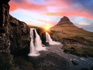 La cascade de Kirkjufellsfoss coule au premier plan au coucher du soleil.