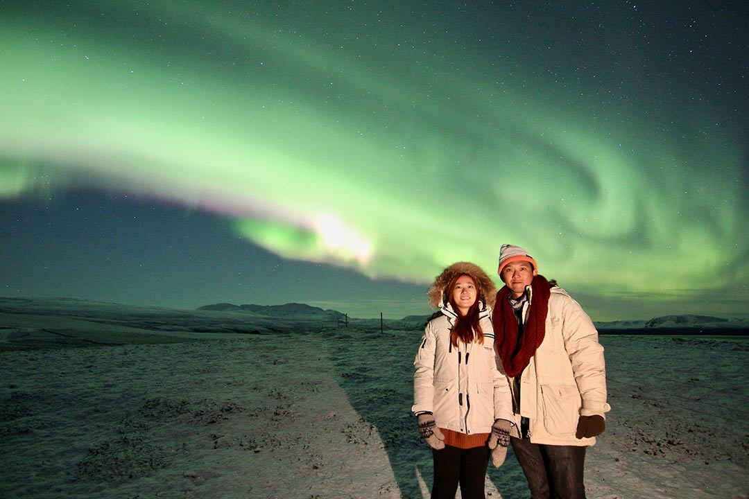 A happy couple enjoying the northern lights