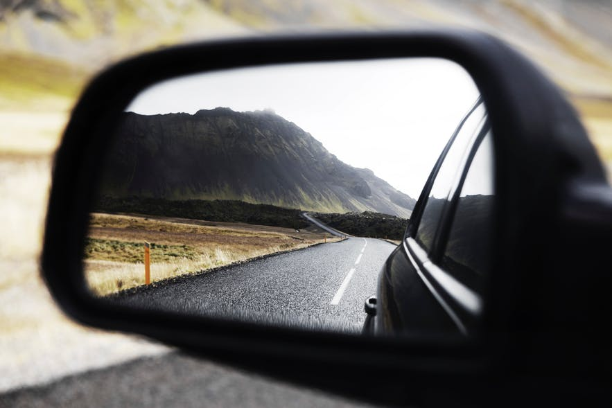 An image of the beautiful landscape of Iceland in a side view mirror