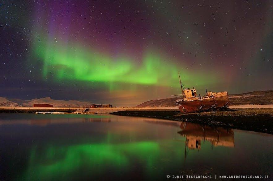 แสงเหนือปรากฏเหนือซากเรือประมงที่ถูกทิ้งในฟยอร์ดทางตะวันตกของไอซ์แลนด์