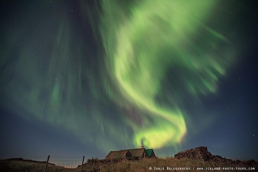Zielona zorza polarna tańcząca na zimowym niebie.