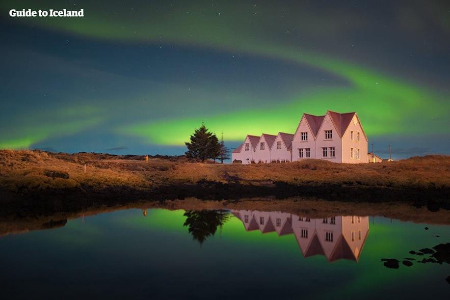Virvlende nordlys rundt en islandsk gård.