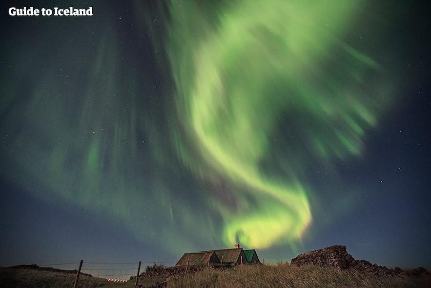 Het noorderlicht dat boven een IJslands huis danst.