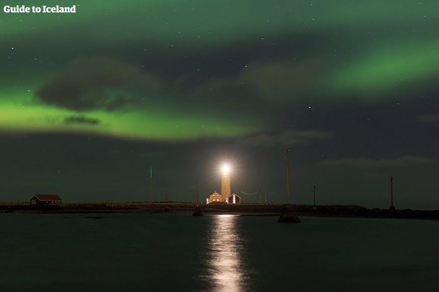 Het noorderlicht dat boven een IJslandse vuurtoren danst.