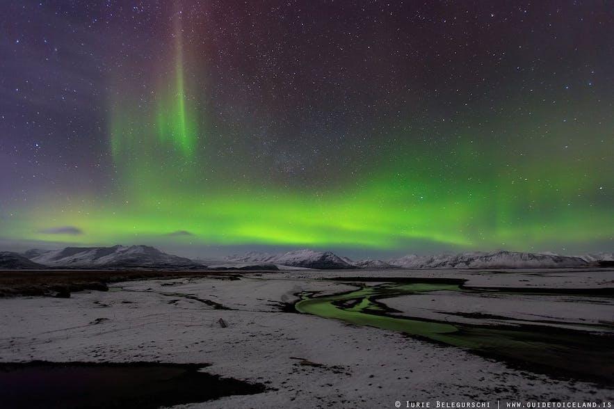 Die Nordlichter über schneebedeckten Lavafeldern und majestätischen Bergen