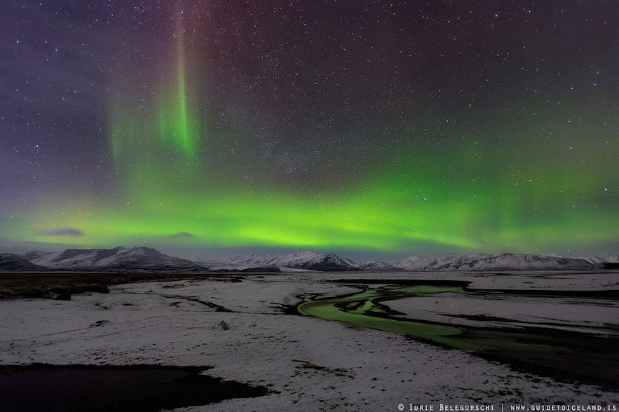 The Northern Lights above snow-covered lava fields and majestic mountains.