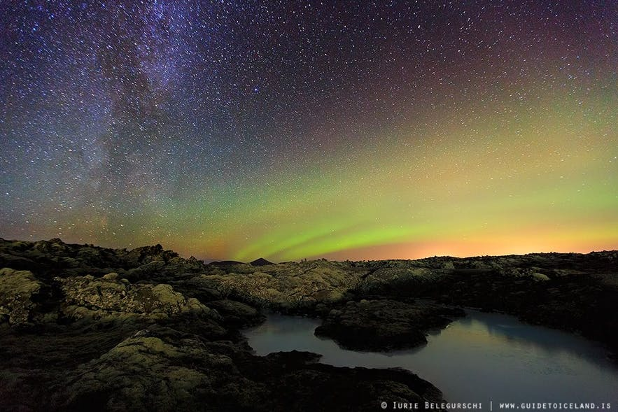 A particularly starry night with the Northern Lights appearing like a cosmic sunrise by the horizon.