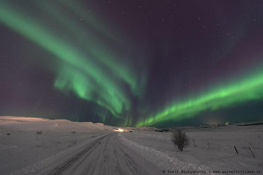 Eine einsame, schneebedeckte Straße, über der die Polarlichter in die Unendlichkeit zu führen scheinen