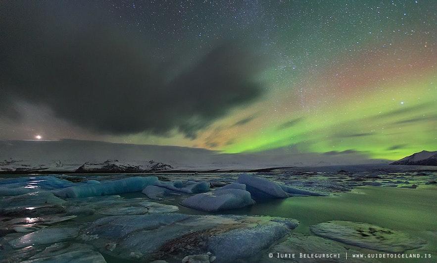 Aurores polaires et étoiles au-dessus de la lagune glaciaire en Islande