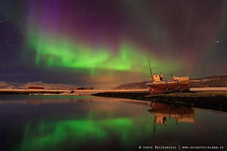 一艘旧船停靠在极光中