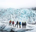 A group of happy travelers taking in the view from the top of a glacier.