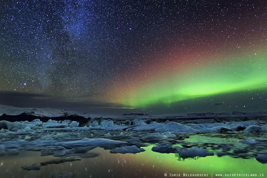 Sterne und Polarlichter spiegeln sich im tiefen See von Jökulsárlón
