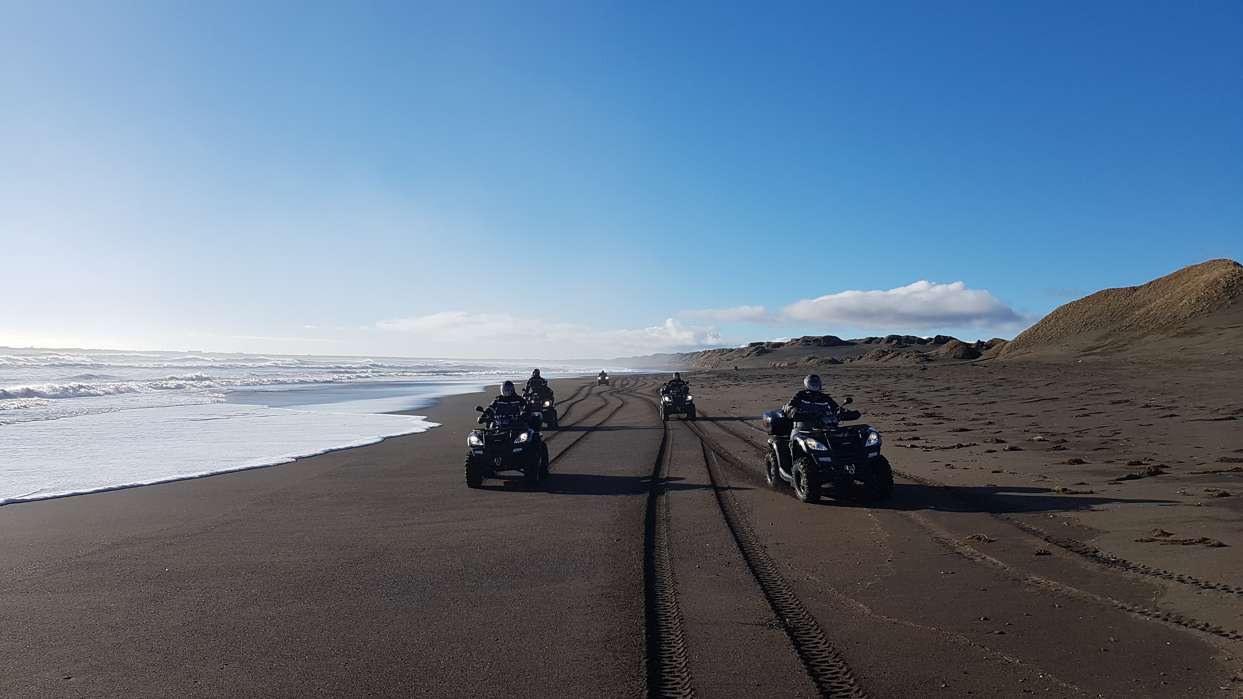 Travellers on ATV's, driving on a Black Sand Beach.