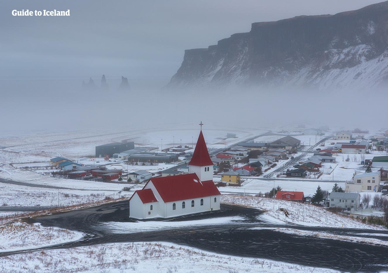 Eine frische Schicht Pulverschnee bedeckt den bildhübschen Ort Vík an der Südküste von Island.
