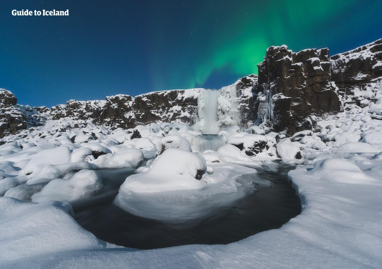 Die Polarlichter tanzen am Himmel über dem Wasserfall Öxarárfoss im Þingvellir-Nationalpark.