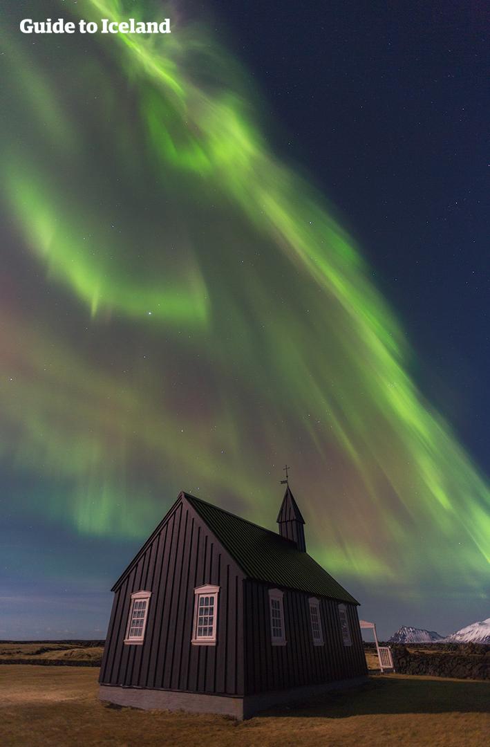 แสงออโรร่าเต้นระบำเหนือโบสถ์ดำที่ปูดิร์บนคาบสมุทรสไนล์แฟลซเนส