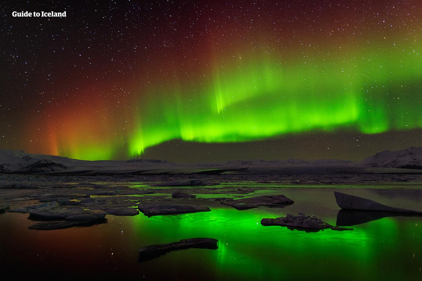 Die Nordlichter spiegeln sich im ruhig daliegenden Wasser der Gletscherlagune Jökulsarlon.