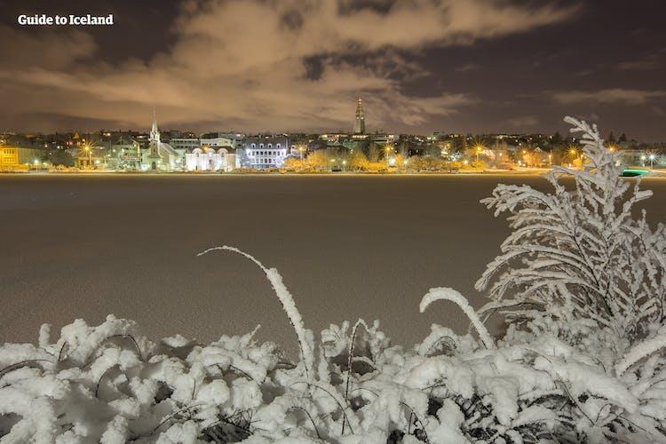 Im Dämmerlicht des Winternachmittags laufen Menschen über den gefrorenen See Tjörnin in Reykjavik.