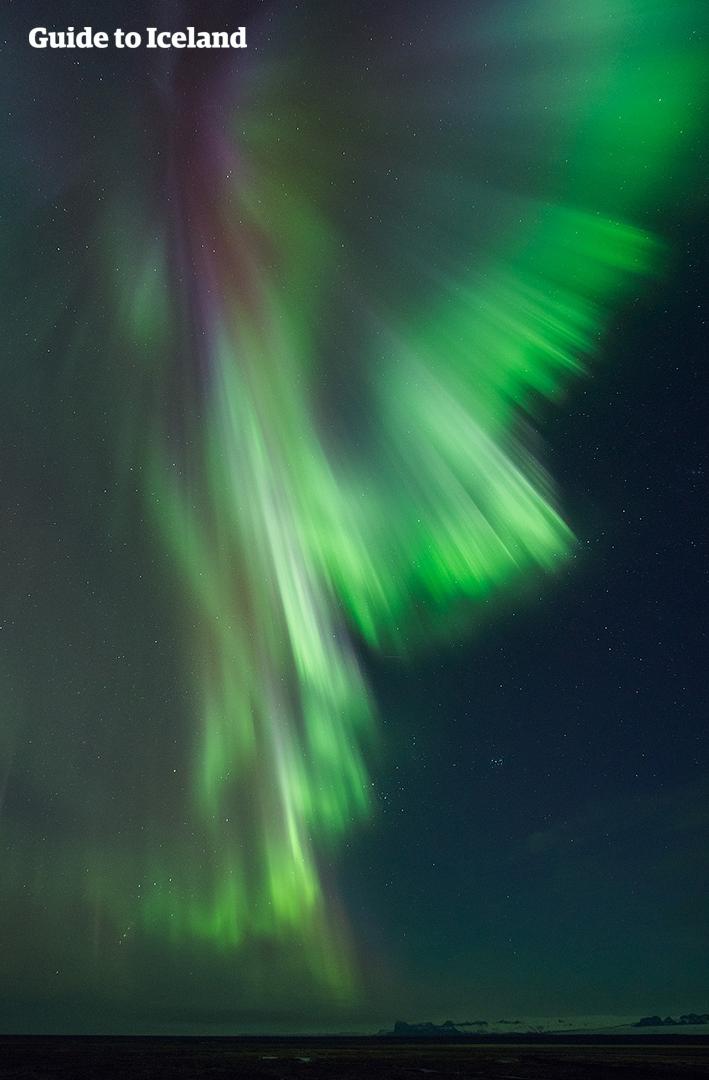 아이슬란드의 어둠이 짙게 깔린 겨울밤, 화려한 공연을 펼치는 오로라.
