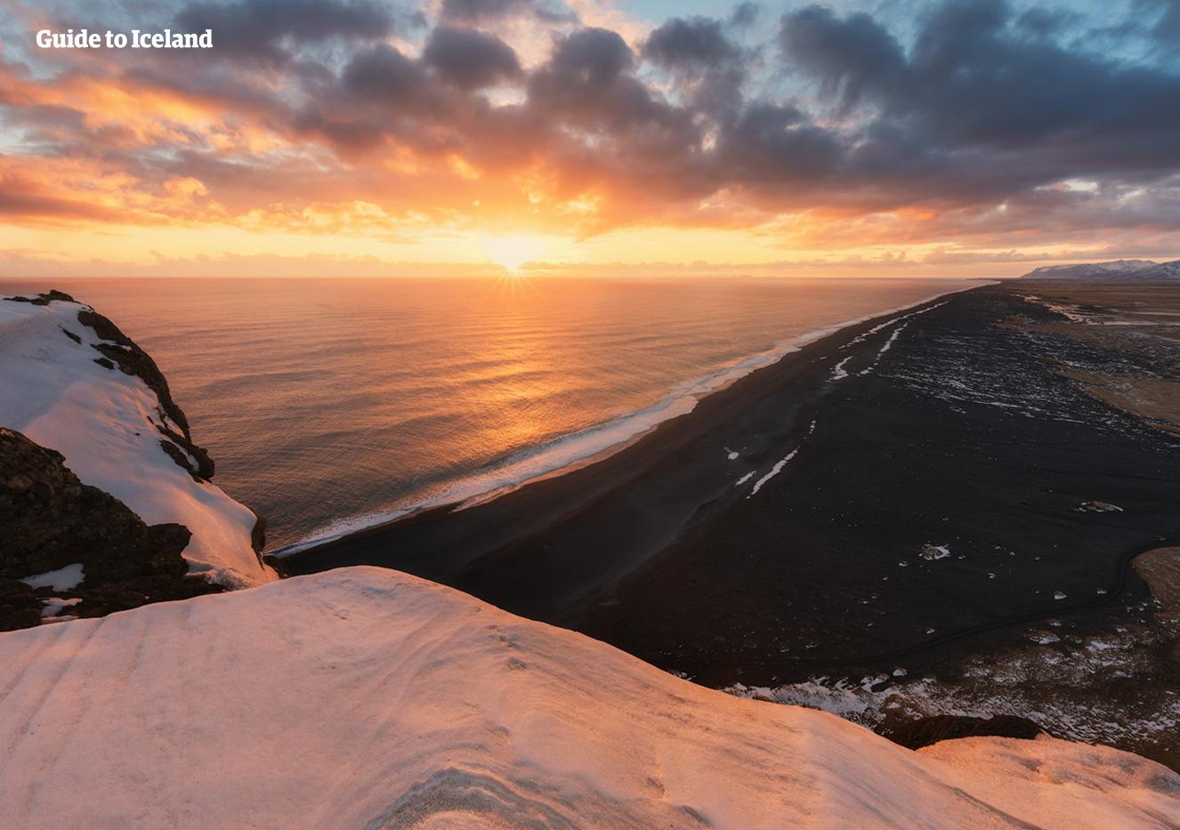 Das winterliche Farbenspiel an der Südküste mit einem roten Abendhimmel über zartem, weißem Schnee auf dem schwarzen Sandstrand Reynisfjara.
