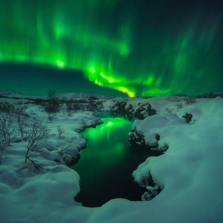 Norrsken över ett snötäckt landskap