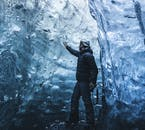 A man in vatnajokull ice cave exploring the shapes of the ice