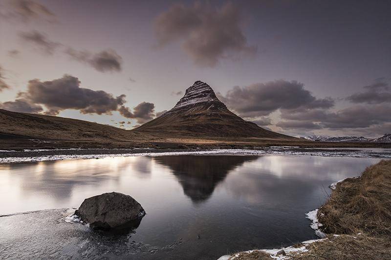 La montaña Kirkjufell con vistas a un lago prístino en la península de Snaefellsnes