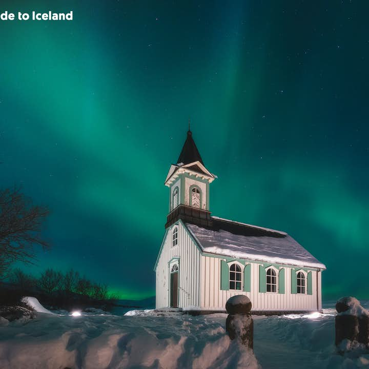 Thingvallakirkja church in winter, covered in snow, with northern lights in the background