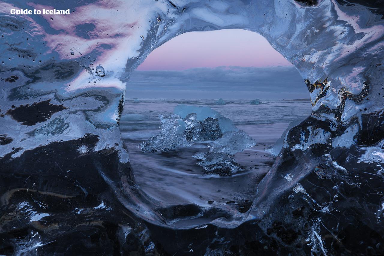 Om du bor på ett hotell nära issjön Jökulsárlón när du är ute på sommarrundturen där du kör själv kan du njuta av midnattssolen över Diamantstranden.