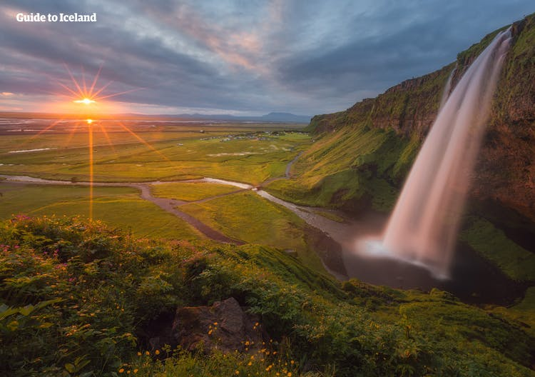 The magical cascade of Seljalandsfoss waterfall bathed in the light of the setting summer sun.