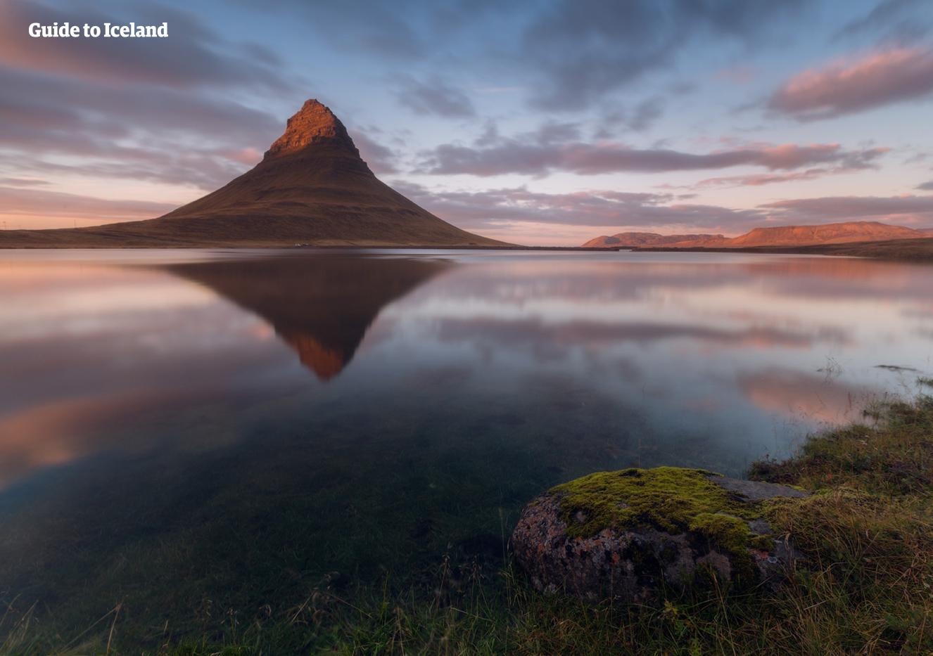Berget Kirkjufell avspeglat i en sjö under en midsommarkväll på Island.