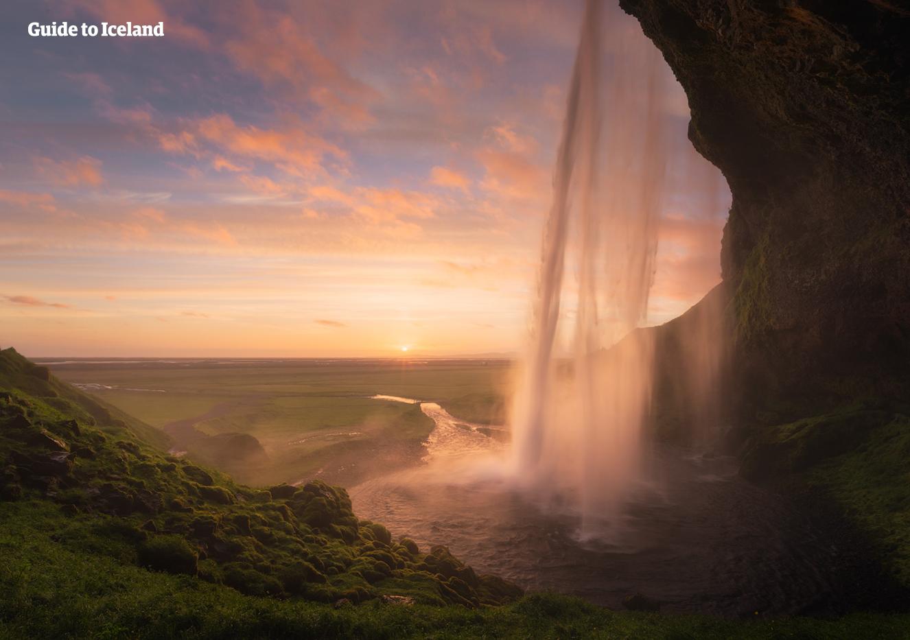 Runt sommarsolståndet i juni kan besökarna stå bakom vattenfallet Seljalandsfoss vid midnatt och se solen där den aldrig går nedanför den södra horisonten.