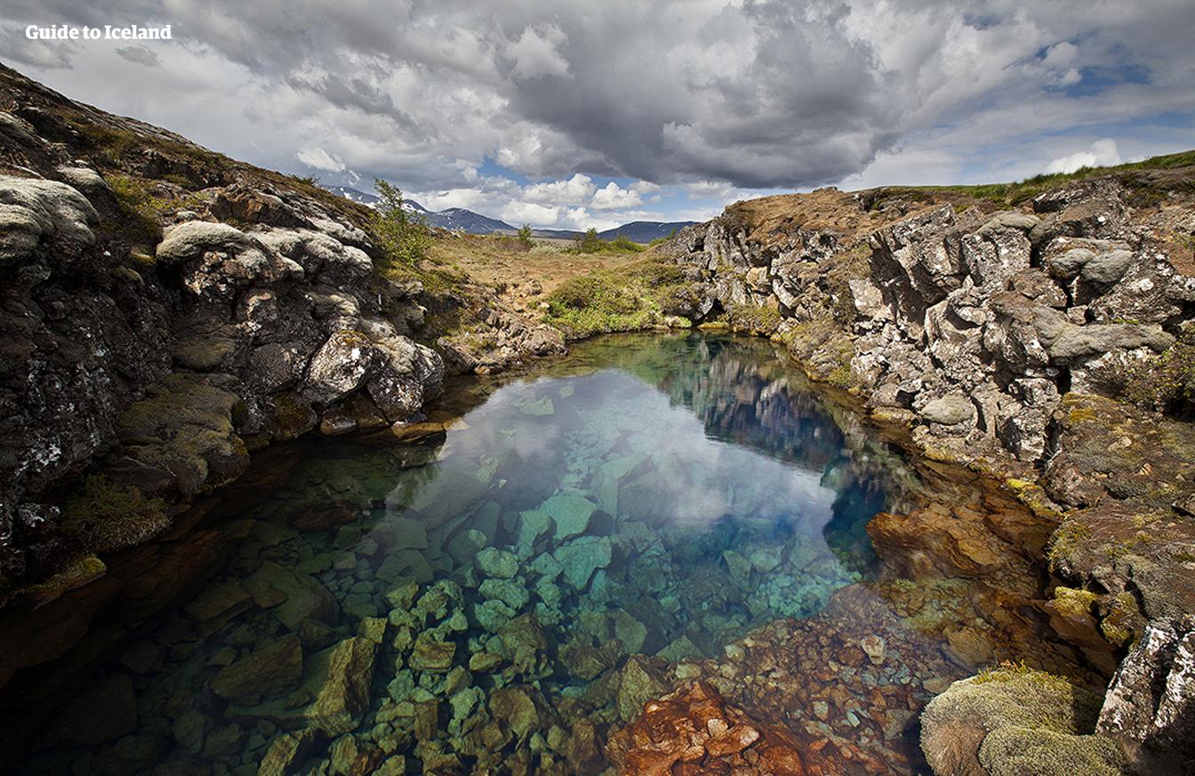 Smeltwater van de Langjökull-gletsjer zakt weg in een lavaveld en stroomt ondergronds naar ravijnen in Nationaal park Þingvellir. Dit lange filtratieproces heeft tot gevolg dat de bronnen hier het hele jaar door tot de bronnen behoren die de beste natuurlijke zichtbaarheid ter wereld hebben.