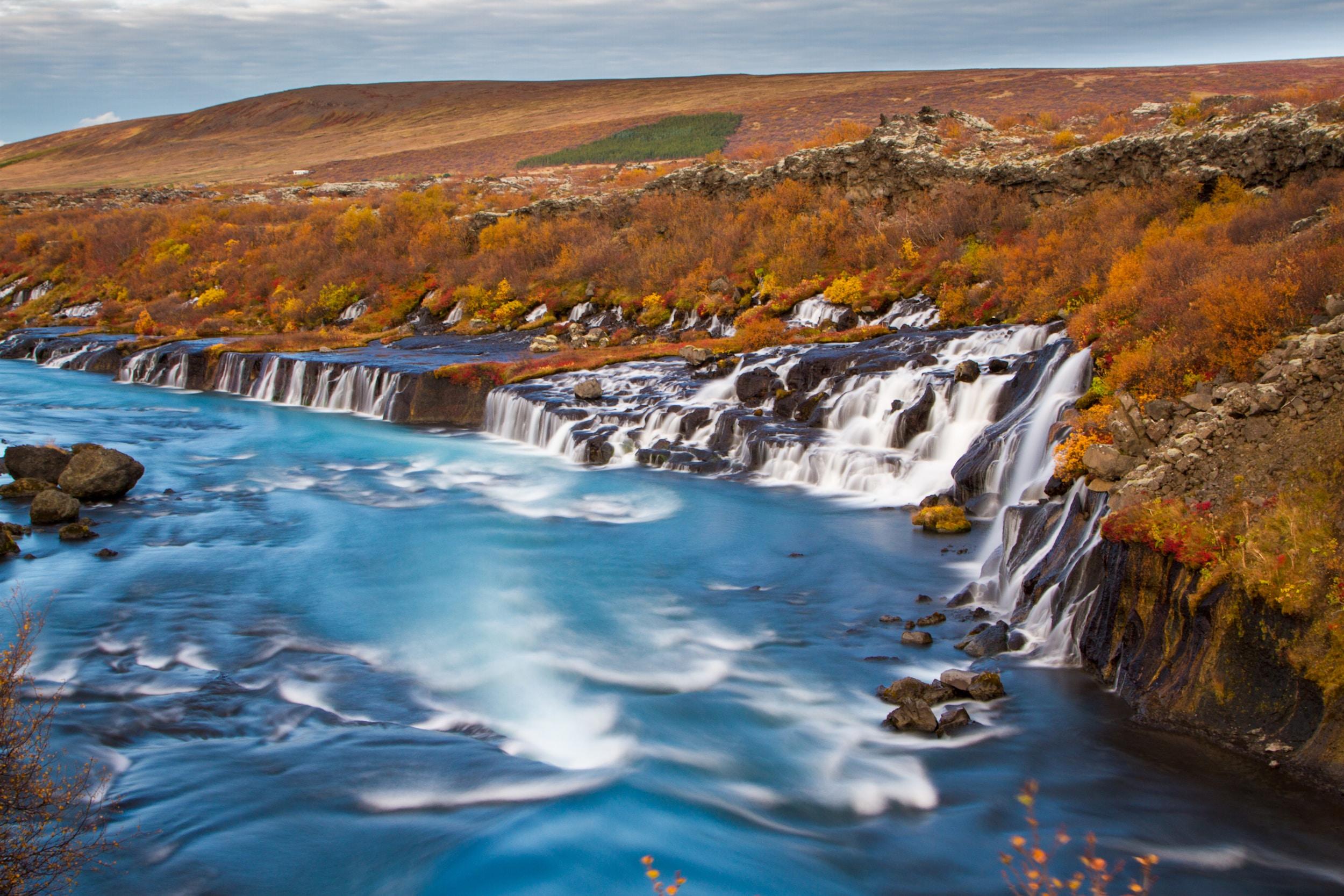Wasserfälle fließen in einen atemberaubenden Fluss im Westen Islands.