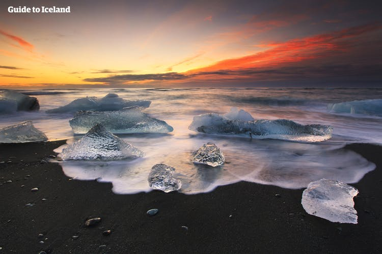 A chunk of ice that lays on the Diamond Beach is illuminated in the light of the midnight sun at its lowest point.